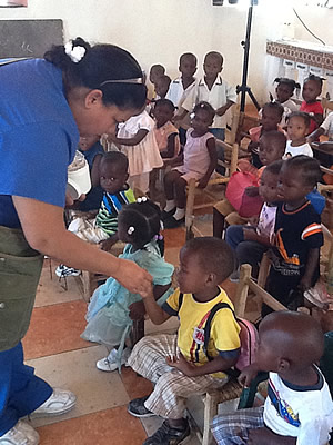 Lydie distributing deworming tablets to children